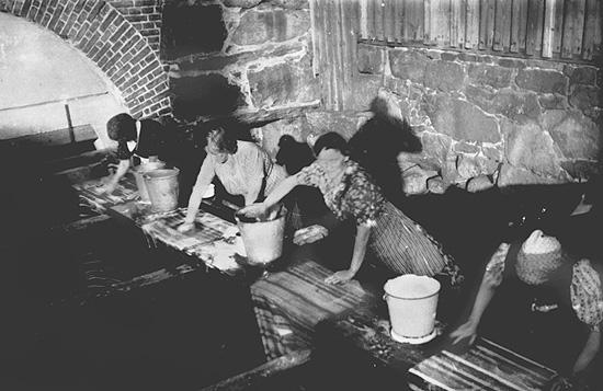 Kvinnor tvättar i ett, så kallat, brôgghus.