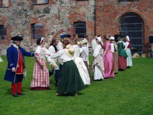Gustavianerna dansar sirliga danser framför Gräfsnäs slottsruin. Längst till vänster ses Ulf Leonardzon, dagen till ära iförd ny civil dräkt. Foto: Anna Jolfors 9/7 2011.