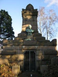 Viktor Rydbergs mausoleum har försetts med en gallergrind. Man ser tre värmeljus. (Foto: Lars Gahrn.)