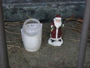 Mellan gallergrinden och den kopparbeslagna dörren står två värmeljus och en liten tomte. Den svenska jultomtens fader är inte glömd!
