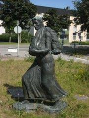 Barfota kvinna bär tyger till förläggargården. Staty i Kinna. Foto: Lars Gahrn.