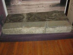 Gravstenen stod upp en bit ur golvet och har senare stått ut en bit ur tornväggen.