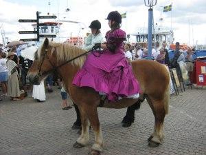 Hästflickor med gammaldags damsadlar och klänningar men nutida ridhjälmar red före kungens vagn.