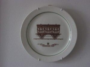 Järnvägsvagnen ser ut som tre sammanbyggda hästdragna kupévagnar. Text i bild: Personvagn 1860.