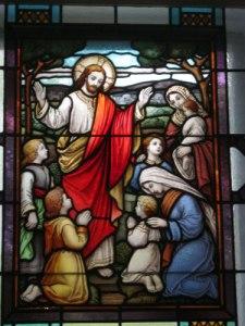 Jesus välsignar knäböjande barn.