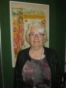 Konstnärinnan Birgitta Arkenback vid ett av de diplom, som hon har formgivit.