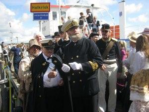 Kungen och hans följe stiger i land och välkomnas av kommendanten på Carlstens fästning.