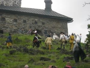 Mödosamt klättrar angriparna uppför bergssidan. Götiska Förbundets stormästare Bengt P. Gustafsson (med megafon och slängkappa) kommenterar framryckningen.