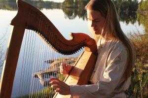 Oscar Jacobsson spelar på sin harpa.