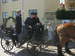 Konungen står upp i vagnen och hälsar på sina undersåtar.