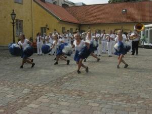 Kungälvs drillflickor dansar med skicklighet och smittande glädje. I bakgrunden står Kungälvs musikkår. Foto: Lars Gahrn.
