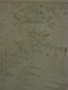 Rökmoln väller ut ur tornet. Detalj av reliefen. Foto: Lars Gahrn.