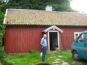 Anders Johansson vid boningshuset i Rösets gård. Bakom huset står skogen tät.