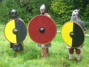 Tre vikingar med stora sköldar. Två sköldar har samma färger som Västergötlands landskapsvapen och fotbollslaget Elfsborg.