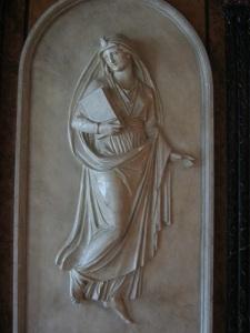 I hörsalen finns flera vackra reliefer, bland andra denna, som visar teologin, en kvinna med en bok (sannolikt bibeln) under armen och den helige Andes låga över huvudet.