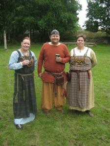 Tre medlemmar i vikingatida klädedräkter.