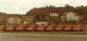 """""""Liftdumprar"""" (lastbilar, som kan lyfta av och på containrar), fotograferade med stadsdelen Trädgården i bakgrunden."""