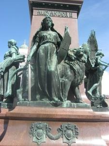 Suomis dotter (Finland) med Finlands lejon och lagen (Lex) som sköld.