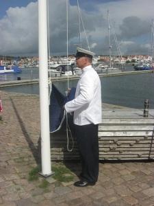 Peter Jitzmark, klädd i seglarkläder, hissade Finlands flaggor med värdighet och stor säkerhet. Foto: Lars Gahrn.