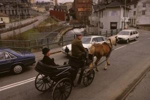 Sven Olof Olsson kör biskop Blocks åkvagn med kyrkoherde Herman Gustavsson över Forsebron på väg mot Lantbruksmuseet i Götaforsliden. (Foto: Mölndals Hembygdsförenings bildarkiv.)