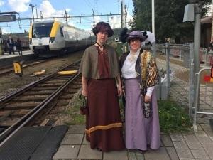 Två damer i kläder från förra sekelskiftet. I bakgrunden ses ett nutida tåg, som i detta sammanhang är opassande modernt.