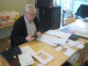 Föreningens skattmästare Sven-Olof Ask blickar ut över alla lappar med uppgifter om vem som skall faktureras.