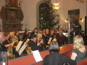 Christina Lundin dirigerar Mölnlycke Blåsorkester, medan Jenny Björkqvist sitter i avbytarbänken tillsammans med Stina Klintbom, som sjöng till vissa av musikstyckena. Foto: Lars Gahrn.