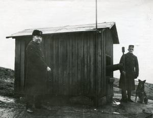 Brandkanonens eldrör sticker ut ur kanonhuset på Störtfjället. Fjärdingsman J. F. Johansson håller i avfyrningssnöret. Till höger ses Andor Danielsson och hunden Bill. Foto: Knut Kjellman 1921 eller 1922, Mölndals Hembygdsförenings bildarkiv.
