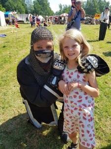 Flickan skräms inte av Svarta Riddarens mask. Bild från Lödöse medeltidsdagar.