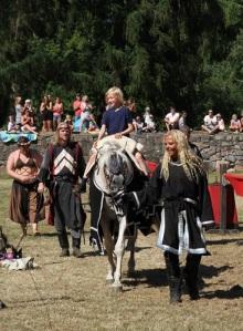 Efter torneringen får ett av barnen rida på Svarta Riddarens häst. Foto: Agneta Elisabeth Muhr.
