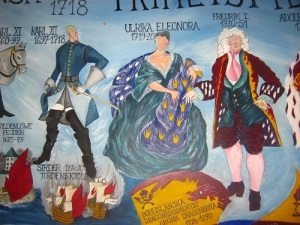 Huvudpersonerna i slutet av 1718: Karl XII, hans syster Ulrika Eleonora och hans svåger Fredrik av Hessen. Detalj av väggmålning i Bohusläns museum. Foto: Lars Gahrn.