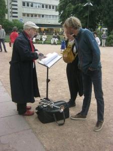 Salomon Helperin bläddrar i sina noter och dryftar lämplig melodi med ett par åhörare. Det blev Happy Birthday. Foto: Lars Gahrn.