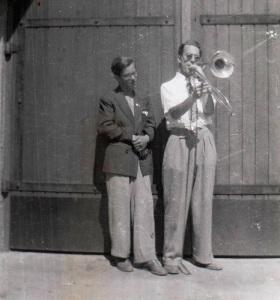 Bert och Ingvar Leion, fotograferade framför stora porten i Samuelsons strumpfabrik (Kvarnbygatan 12) år 1947. Ingvar Leion tränar trombon, vänd mot forsen. Hans bror Bert lyssnar.